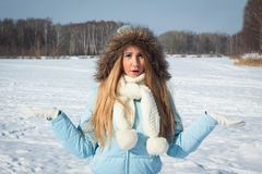 Surprised girl in the park. Frosty morning in the park, snowy winter. Surprised girl in a blue jacket and white scarf in the park. Frosty morning in the park Stock Photography