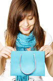Surprised girl with blue shopping bag. Surprised young girl with blue shopping bag in her hands Stock Image