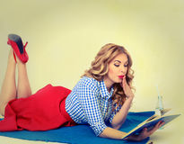 Surprised girl with a book in hand retro. Surprised blond woman reading a book lying on a plaid Royalty Free Stock Image