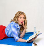 Surprised girl with a book in hand retro. Surprised blond woman reading a book lying on a plaid Royalty Free Stock Photos