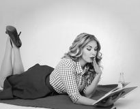 Surprised girl with a book in hand retro. Surprised blond woman reading a book lying on a plaid Stock Photo
