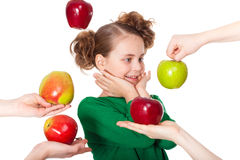 Surprised girl choose among proposed apples Stock Photography