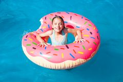 Surprised girl on a colorful inflatable donut Royalty Free Stock Images
