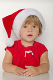 Surprised  girl in costume of Santa Claus at table Stock Photos