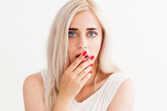 Surprised girl covers her mouth. And her eyes wide open. A conceptual photo on a white background Royalty Free Stock Photo
