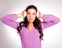 Surprised  girl with earmuff. Pretty young surprised brunette woman wearing pink earmuff Royalty Free Stock Photos