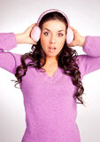 Surprised  girl with earmuff. Pretty young surprised brunette woman wearing pink earmuff Stock Images
