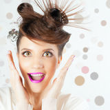 Surprised girl with fancy hairstyle at white blurred background stock image