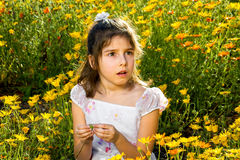 Surprised Girl in a Flower Bed. A young girl sits in a bed of wild flowers and looks to the side of the frame with a surprised expression on her face Stock Photos