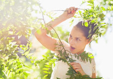 Surprised girl in foliage looking on copy space Stock Photo
