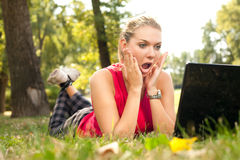 Surprised girl in front of laptop Stock Images