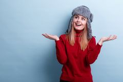 Surprised girl, in a fur hat and sweets, raised hands in surprise and looked away with a smile. Blue background. Surprised young blonde girl, dressed in a warm Stock Image