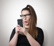 Surprised girl with glasses and a smartphone Stock Photo