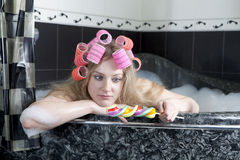 Surprised girl with hair curlers take a buth Stock Photos