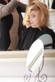 Surprised girl by hairdresser in salon Royalty Free Stock Photo
