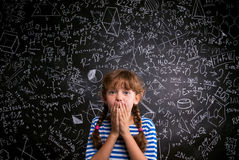 Surprised girl, hands on mouth, blackboard with mathematical sym Royalty Free Stock Photography