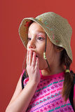 Surprised girl with a hat. Girl with a hat and braids holding a hand over mouth and acting surprised Stock Photography