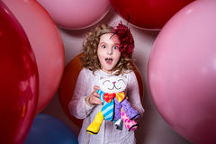 Surprised girl in a hat of the bow against the backdrop of a large bright airy rubber balls royalty free stock photo