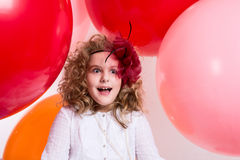 Surprised girl in a hat of the bow against the backdrop of a large bright airy rubber balls royalty free stock photos