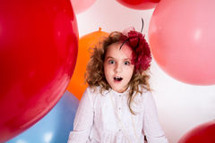 Surprised girl in a hat of the bow against the backdrop of a large bright airy rubber balls stock photography