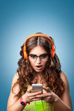 Surprised girl in headphones listening music and looking on phone Stock Photos