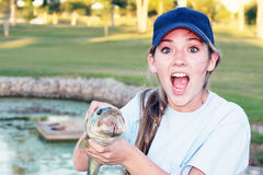 Surprised Girl Holding Fish. Teen girl wearing a blue hat holding a Large Mouth Bass on a golf course pond Royalty Free Stock Images