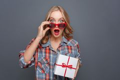 Surprised girl is holding a gift in her hands. She diddn`t expect that. Young lady is looking straight forward and. Holding her glasses on the nose. Isolated on Stock Images
