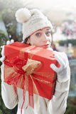Surprised girl, holding tight, her gift. Surprised girl in a store, holding tight, her gift Stock Image