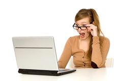 Surprised girl with laptop. Teenage girl sitting with laptop royalty free stock image