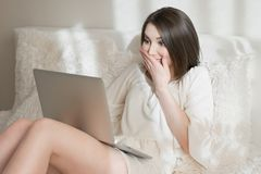 Surprised girl with a laptop on the bed stock images