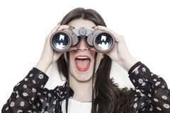 Surprised girl looking through binoculars Stock Photo
