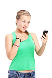 Surprised girl looking at a cell phone Stock Photography