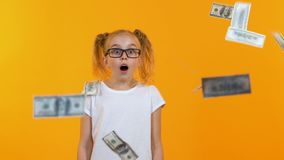 Surprised girl looking at falling from sky dollars, clever girl win prize, grant