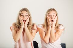 Surprised girl looking at her sister twin over white background Stock Image