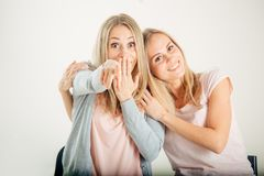 Surprised girl looking at her sister twin over white background Royalty Free Stock Image