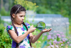 Surprised girl looking through magnifying glass on beetle Royalty Free Stock Photos