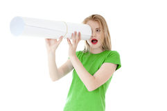 Surprised girl looking through a paper telescope hole. Stock Images