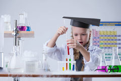 Surprised girl looking at test tubes with reagents. Close-up Royalty Free Stock Image