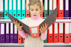 Surprised girl looks folder and stands near to shelves stock photo