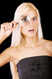 Surprised girl looks in a magnifier Royalty Free Stock Photo