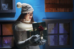 Surprised girl opening Christmas gifts Royalty Free Stock Images