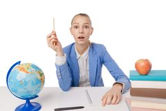 Surprised girl with  pencil sitting at table Royalty Free Stock Images