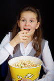 Surprised girl with popcorn on a black background Royalty Free Stock Image