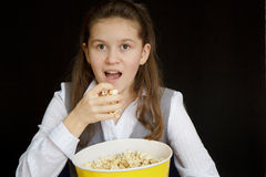 Surprised girl with popcorn on a black background Royalty Free Stock Photos