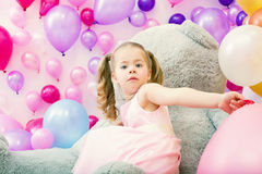 Surprised girl posing at camera with balloons Stock Image
