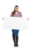 Surprised Girl And Poster. Surprised young woman in jeans, black boots and lumberjack shirt standing and holding white placard. Full length studio shot  on white Stock Photo