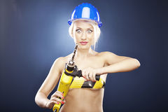 Surprised girl with power drill and helmet Stock Photo