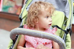 Surprised girl in the pram. Royalty Free Stock Photography