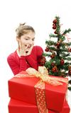 Surprised girl with presents near a christmas tree. Isolated Stock Images