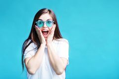 The Surprised Girl. Pretty caucasian brunette girl wears sunglasses have happy surprised face expression on blue background royalty free stock photos